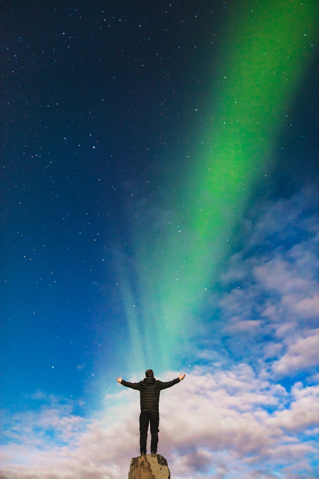 Man Standing on Rock Under Green Aurora Borealis And White Clouds by Joshua-Earle